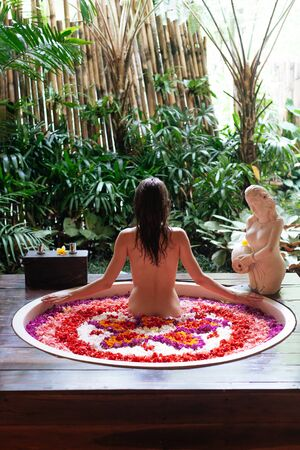 Back view of Woman relaxing in round outdoor bath with tropical flowers, organic skin care, luxury spa hotel, lifestyle photo.