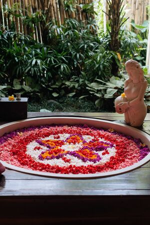 Stone round bath tub with flower shaped petals in pink,red,white colors near window with jungle view. Organic spa relaxation in luxury Bali bathroom 版權商用圖片