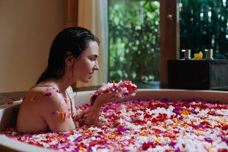 Woman enjoying smell of flowers petals in her hands in round outdoor bath with tropical flowers, organic skin care, luxury spa hotel, lifestyle photo.