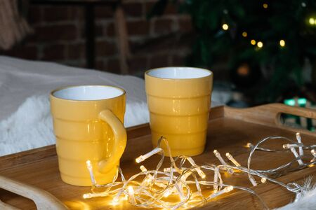 Cozy Christmas composition Two yellow mug with hot drinks on a wooden tray stand on the bed with a fluffy blanket against the background of festive tree in loft interior room in decor in garlands