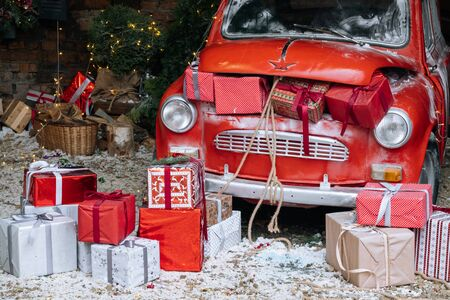 New Year decorated exterior with trunk full of Christmas gifts of retro red car with snow and festive lights and garlands outside of house. 版權商用圖片