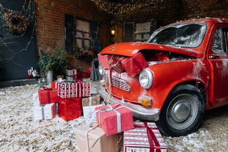 Christmas gifts packed with red,white,craft paper and tapes under decorated retro red car with trunk full of New Year gifts on snow and festive lights and garlands outside of house 版權商用圖片