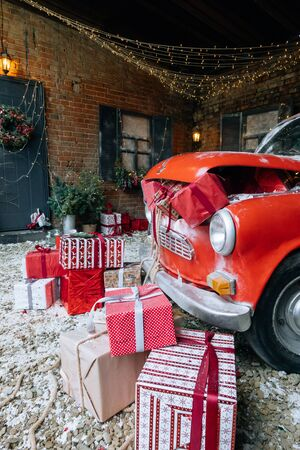 Christmas gifts packed with red,white,craft paper and tapes under decorated retro red car with trunk full of New Year gifts on snow and festive lights and garlands outside of house Stock Photo