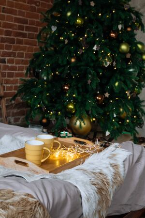 Two yellow mug with hot drinks on a wooden tray stand on the bed with a fluffy blanket against the background of christmas tree in cozy loft interior room in decor in garlands 版權商用圖片