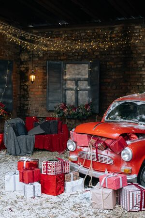 New Year and magic Christmas decorated exterior with retro red car with many gifts and many festive New Year lights and garlands outside of house with sofa. 版權商用圖片