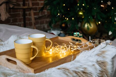 Cozy Christmas composition, two yellow mug with hot drinks on a wooden tray stand on the bed with a fluffy blanket against the background of festive tree in loft interior room in decor in garlands. 版權商用圖片