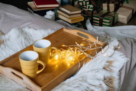 Cozy Christmas composition, two yellow mug with hot drinks on a wooden tray stand on the bed with a fluffy blanket against the background of festive tree in loft interior room in decor in garlands