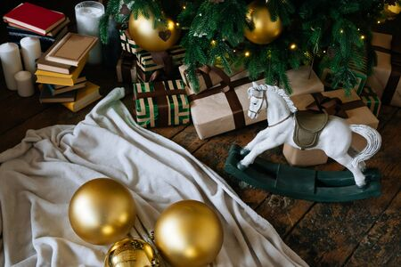 Holiday, New Years gift boxes and wooden horse toy under decorated Christmas tree with golden baubles, garland in cozy loft interior