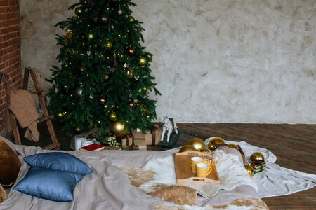 Stylish Christmas loft interior,cozy bedroom with wooden bed and a lot of lights with a decorated Christmas tree and a garland.