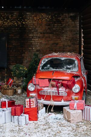 New Year decorated exterior with trunk full of Christmas gifts of retro red car with snow and festive lights and garlands outside of house. Stock Photo