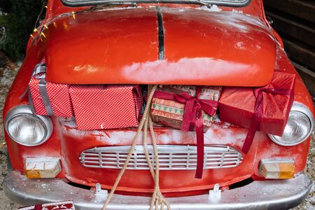Close up car trunk full of Christmas gifts of retro red car in magic New Year decorated exterior with festive lights, garlands outside of house with sofa.