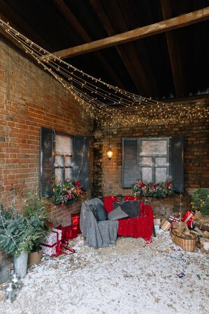 New Year and magic decorated exterior with Christmas tree, many gifts and festive lights and garlands outside of house with sofa and plaid on background of brick wall 版權商用圖片