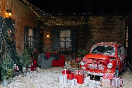 New Year and magic Christmas decorated exterior with retro red car with many gifts and festive lights and garlands outside of house with sofa.