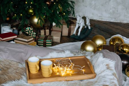Two yellow mug with hot drinks on a wooden tray stand on the bed with a fluffy blanket against the background of christmas tree in cozy loft interior room, in decor in garlands.. 版權商用圖片