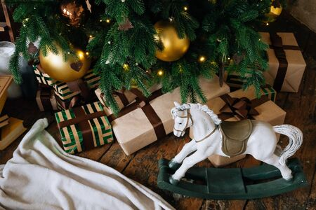 Holiday, New Years gift boxes and wooden horse toy under decorated Christmas tree with golden baubles, garland in cozy loft interior.