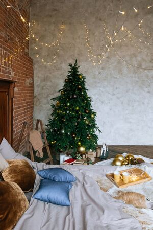 Stylish Christmas interior, bedroom with a lot of lights. Comfort home in a loft style with a decorated Christmas tree and a garland.