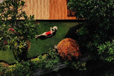 Beautiful slim woman in red bikini and straw hat lies on green grass in garden near swimming pool, sunbathing, enjoys. . view from above. 版權商用圖片