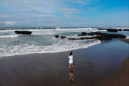Aerial view of unrecognizable woman in white dress walking near ocean and enjoy summer day on beach. Vacation in Bali. Photo from drone. Copy space. Photo from drone Copy space