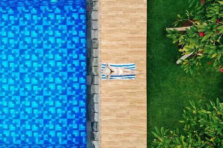 Enjoying suntan. Vacation concept. Top view of slim young woman in white bikini and straw hat lying on towel near swimming pool. Back view, without face.