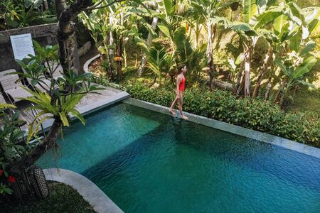 Woman in red bikini in a private pool in Bali admires a beautiful view of the palm trees.Luxury holiday.Woman resting in the pool on Bali. Vacation concept Space for text. 版權商用圖片 - 138990410