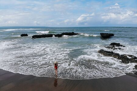 Girl in red swimsuit and straw hat enjoy summer day near ocean beach with black sand. Vacation in Bali. Photo from drone. Copy space.