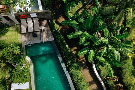 Top view of unrecognizable slim young woman in beige bikini relaxing and sunbathe near luxury swimming pool in green tropic in Ubud.Vacation concept. Drone photo. 版權商用圖片 - 138990434