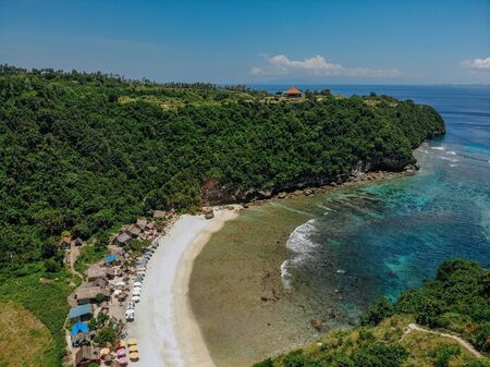 beautiful bay beach with turquoise ocean water with many umbrellas top view aerial photo with white beach and jungle of tropical island. 版權商用圖片