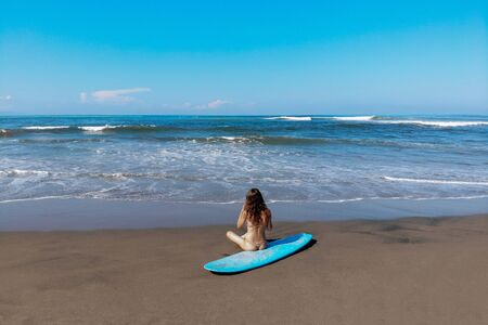 beautiful sporty surfing woman in sexy bikini sit near longboard surf surfboard board on beach before surfing. Modern active sport lifestyle and summer vacation.