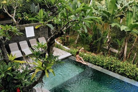 Back view of woman in bikini in a private pool in Bali admires a beautiful view of the palm trees.Luxury holiday.Girl resting on the island of Bali. Copy space. Vacation concept.