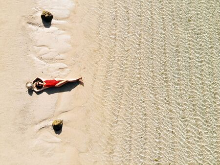 Aerial drone view of young woman in red bikini sunbathe on beach with white sand, turquoise water of the Indian Ocean. Bali Island, Indonesia. Tropical background and travel concept. 版權商用圖片