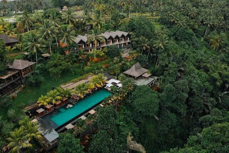 Aerial view of luxury hotel with straw roof villas and pools in tropical jungle and palm trees. Luxurious villa, pavilion in forest, Ubud, Bali.