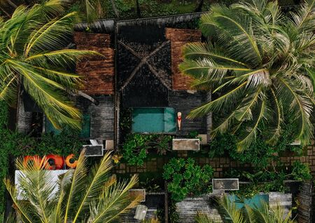 Aerial drone photo of unrecognizable Woman in red swimsuit relaxing near private pool with palm trees around, Bali. Tropical background and travel concept