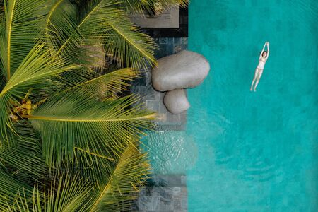 Top view of slim young woman in bikini swimming in luxury pool and palm trees.Vacation concept. Drone photo.