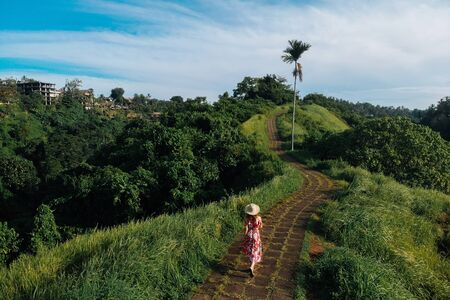 Unrecognizable woman walking on Campuhan Ridge way of artists, in Bali, Ubud. Beautiful calm sunny morning.
