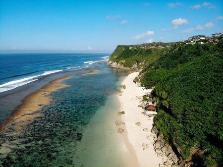 Aerial drone view of tropical island with white beach and blue clear water and jungle. Bali Indonesia. Tropical background and travel concept.