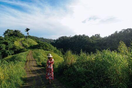 Back view of woman walking on Campuhan Ridge way of artists, in Bali, Ubud. Drone photo Copy space. 版權商用圖片