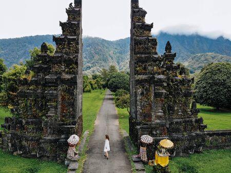 Tourist woman walking through Traditional Balinese Hindu gate Candi Bentar close to Bedugul, Bratan lake Bali island Indonesia. Vacation on Bali Drone photo. 版權商用圖片