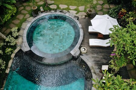 Aerial view of luxury round pool with white umbrellas and sun beds in tropical jungle and palm trees. Luxurious villa, swimming pool in forest, Ubud, Bali. 版權商用圖片