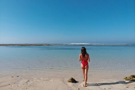 Back view of woman with sexy butt in red bikini enjoying of white sand tropical beach with blue clear water and jungle. Bali Indonesia. Tropical background and travel concept. 版權商用圖片