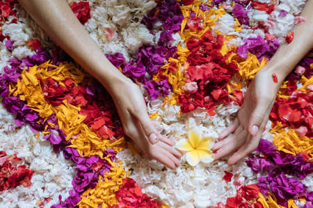 Top view female hands holding frangipani on flowers petals in bath tub in luxury bathroom in hotel. Spa, self care, organic and skin care, beauty treatment concept.