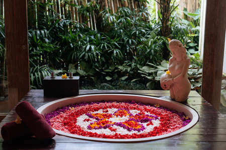 Outdoor jungle view stone round bath tub with flower shaped petals in pink,red,white colors near window. Organic spa relaxation in luxury Bali bathroom. 版權商用圖片