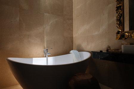 Stone bath tub in luxury interior hotel with sun light from top. Organic spa relaxation in Bali bathroom. 版權商用圖片
