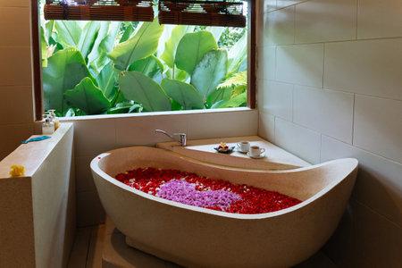 Stone bath tub with heart shaped flower petals near window with jungle view. Organic spa relaxation in luxury Bali bathroom. 版權商用圖片