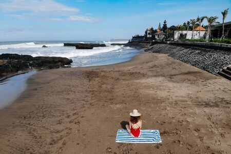 Aerial view of woman in red bikini and straw hat sitting and getting tanned on towel on ocean beach with black sand. Vacation in Bali. Photo from drone