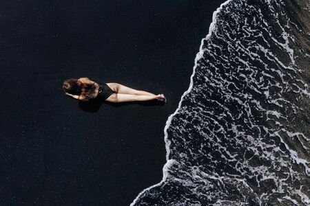 Aerial top view of woman in black swimsuit lying relaxing on the beach with black sand, foaming waves of ocean. Photo from drone. Фото со стока