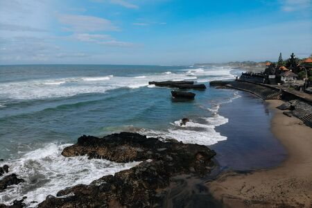 Top view aerial photo from flying drone of amazing sea landscape with turquoise water and temple in Batu Bolong beach Canggu Bali with copy space for advertising text message or content.