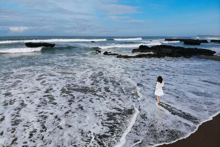 Aerial view of unrecognizable woman in white dress looking at ocean and enjoy summer day on beach with black sand. Vacation in Bali. Photo from drone. Copy space. Photo from drone