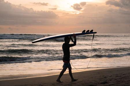 CANGGU, BALI, INDONESIA - FEBRUARY 25, 2019: silhouette of man walking on sea coast with surfboard over head on sunset