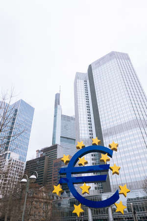 FRANKFURT-AM-MAIN, GERMANY - MARCH 2020: Euro neon sculpture sign in front of the ECB Eurotower in rainy fog weather.