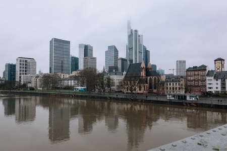 FRANKFURT-AM-MAIN, GERMANY - MARCH 2020: Skyline of downtown financial city center skyscrapers from opposite side of river in fog rainy day.